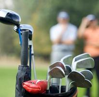 golfklubbar i väska på golfbanan foto