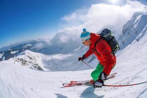 skidåkare skidåkning nedförsbacke i höga berg mot solnedgången