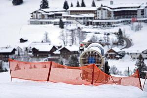 snökanon i förgrunden till ett skidområde foto