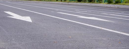 vitmålad pil på svart asfaltväg foto