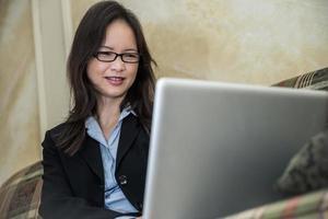 kvinna på soffan med bärbar dator foto