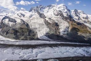 schweiz. ricin, pollux, breithorn, klein matterhorn och gornergletscher från gornergrat foto