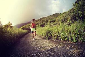 ung fitness kvinna löpare kör på bergsspår foto