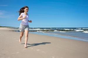 flicka springer på stranden foto