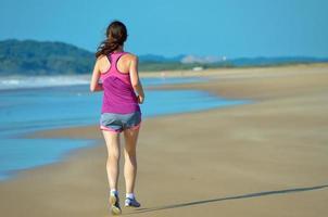 kvinna kör på stranden foto