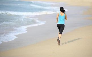 frisk kvinna kör på stranden foto