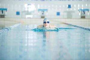 ung flicka i skyddsglasögon som simmar bröstslagsstil foto