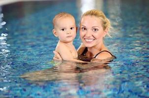 ung glad mamma och lilla son i en pool foto