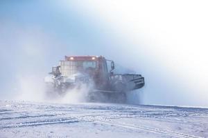 ratrak i spray av snö mot den blå himlen. tonad foto