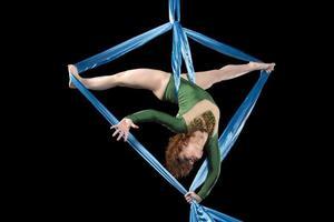 ung gymnast som gör övning på antennsilkar foto