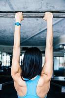 bakifrån porträtt av en kvinna som tränar på gymmet foto
