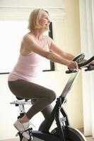 äldre kvinna på motionscykel foto
