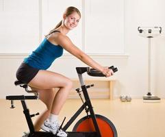 kvinna som rider stationär cykel i hälsoklubb foto