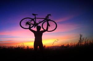 cyklist-flicka vid solnedgången på ängen foto