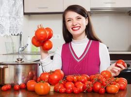 glad kvinna med tomater foto