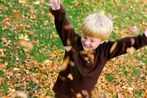 lyckligt litet barn som leker ute i de fallna bladen foto