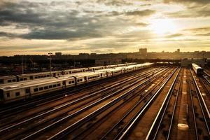 järnvägsstation med tåg under solnedgång