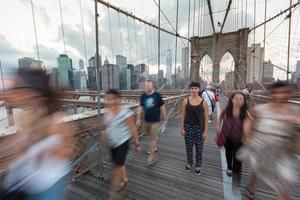 ung kvinna på brooklyn bridge med suddiga människor som passerar foto