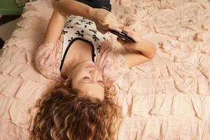 tonårsflicka liggande på sängen med smartphonen foto