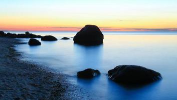 silhuetten vaggar längs stranden foto