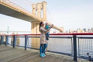 mamma och bedårande liten dotter som fotograferar sig själva foto