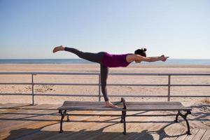 kvinna i yogaställning på strandpromenaden foto