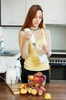 långhårig kvinna som lagar drycker från persikor foto