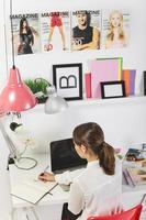 kvinna mode blogger arbetar på ett kreativt kontor foto
