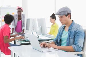 ung kreativ man som använder bärbar dator vid skrivbordet foto