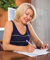 mogen kvinna med finansiella dokument foto