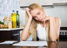 sorglig blond kvinna med finansiella dokument foto