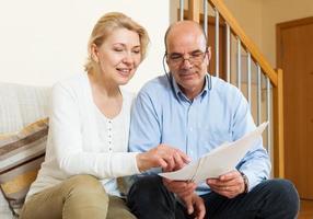 äldre par med dokument hemma foto