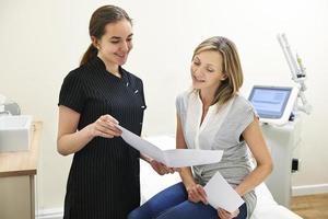 kosmetolog diskuterar behandling med kvinnlig klient foto