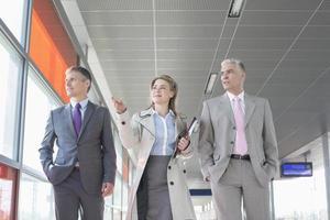 affärsfolk diskuterar medan de går på tågplattformen