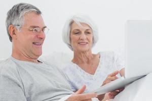 äldre par som använder en bärbar dator tillsammans