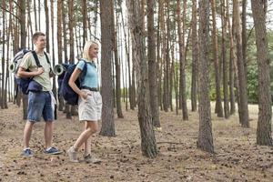 full längd med lyckliga unga par som vandrar i skogen foto