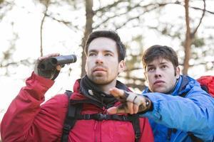 vandrare som visar något till en vän som håller kikare i skogen