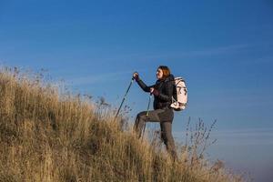 kvinnlig backpacker stiger upp brant kulle foto