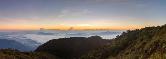 lager av berg och dimma vid solnedgången foto
