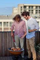 två män som lagar mat på grillen foto