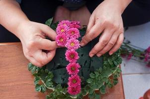 kvinnlig hand ordna blomman för att dekorera foto