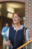 glad kvinnlig mogen student poserar i korridoren foto