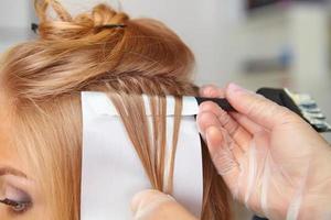 frisör som lägger färg till kvinnans hår foto
