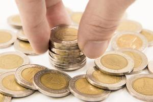 hand sätta mynt till pengar foto