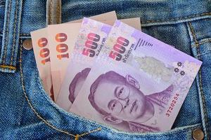 500 och 100 sedlar i mäns blå jeansficka foto