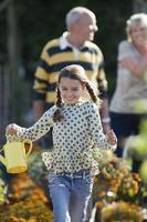 flicka springer i trädgården, håller vattenkanna, morföräldrar står