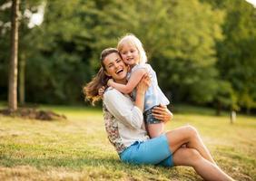 porträtt av glad mamma och baby flicka som kramar i parken