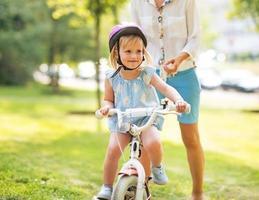 mor och baby flicka som cyklar utomhus foto