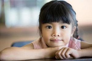 porträtt av en liten asiatisk barnflicka som tittar på kameran foto