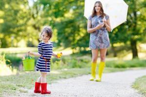 mamma och lilla bedårande barnflickadotter i regnstövlar foto